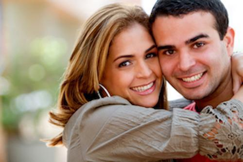 young couple hugging with bright smiles