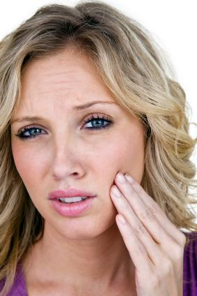 woman in pain holding her hand to the side of her face I emergency dentistry galloway smiles