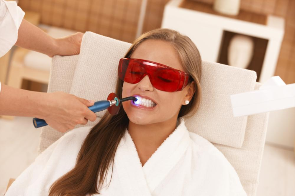woman getting teeth whitened while wearing protective goggles