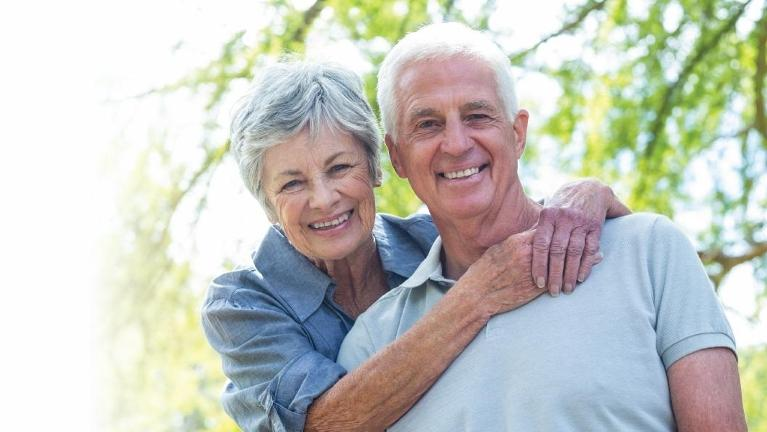 Older couple hugging & smiling