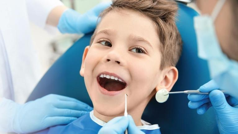Young boy sitting in dental chair smiling